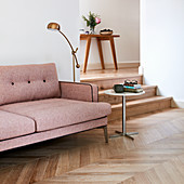 Dusky pink sofa on herringbone parquet floor next to steps leading to hallway