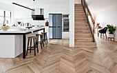 Open-plan kitchen, herringbone parquet floor and stairs in open-plan interior