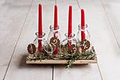 Selbstgemachter Adventskranz aus roten Kerzen in Glasflaschen