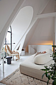 Modern sofa in attic living room with arched window