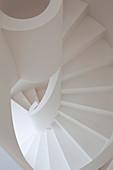 White spiral staircase with masonry balustrade