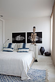 Sculpture and photos of hands above bed in bedroom