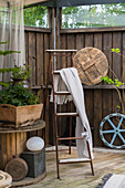 Blanket on wooden ladder on terrace with vintage-style accessories