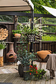 Planters and vintage-style accessories on cosy terrace in garden