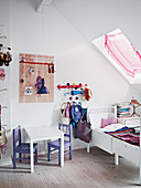 Chairs at table next to extendable bed in child's bedroom