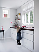 Girl stood on stool in modern kitchen with white floor