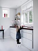 Mädchen auf einem Hocker in moderner Küche mit weißem Boden