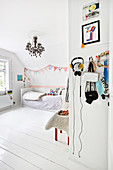 Wooden floor and chandelier in bright child's bedroom decorated entirely in white