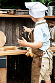 Little boy playing in DIY outdoor play kitchen