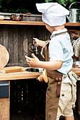 Kleiner Junge spielt an einer selbstgebauten Matschküche
