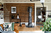 Rustic wooden wall and cast iron stove in classic living room