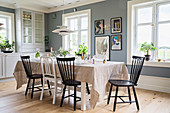 Black and white chairs around set table in dining room