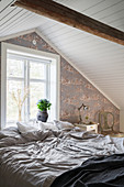 Cosy bedroom with classic wallpaper and sloping ceiling