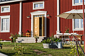 Falu-red Swedish house with open yellow front door and front garden