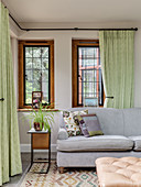 Pale grey sofa set and side table in front of windows with green curtains