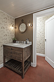 Washstand in corner of bathroom with patterned wallpaper