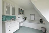 Washstand, mirrored wall cabinet and bathtub in attic bathroom