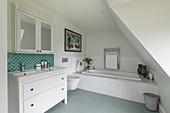 Washstand, mirrored wall cabinet and bathtub in attic bathroom