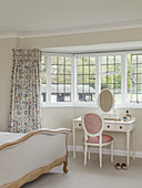 Double bed and dressing table in bright bedroom with bay window