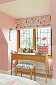 Desk below lattice window in room with pink walls