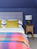 Double bed and bedside cabinet in room with blue walls