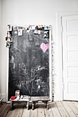 Kreidetafel mit Fotos, davor zwei Holzschemel