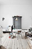 Schreibtisch mit Stuhl, grauer Kleiderschrank und Bett im Kinderzimmer