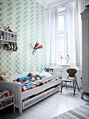 Holzbett im Kinderzimmer mit gemusterter Tapete