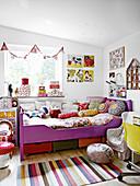 Kinderbett mit Kissen und Steppdecke, Wimpelkette über Fenster und Wanddeko im Mädchenzimmer