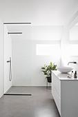 Weißes Badezimmer mit Waschtischmöbel und Duschbereich