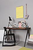 Bilderrahmen, Karten und Lampe auf Schreibtisch und schwarzer Holzstuhl