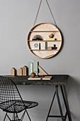 Schreibtisch mit schwarzer Tischplatte, Metallstuhl und rundes Wandregal