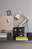 Wooden anglepoise lamp and storage boxes on desk below magnetic pinboard on wall