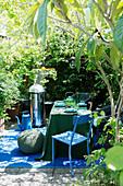 Grill und gedeckter Tisch in Grün und Blau auf sommerlicher Terrasse