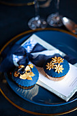 Perfectly decorated cupcakes with dark blue and gold toppings