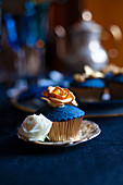 Perfectly decorated cupcake topped with blue icing and gold rose