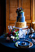 Tiered cake and flowers on table festively set in dark blue