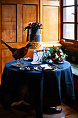 Stuffed pheasant, cake and flowers on table set in blue
