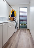 Modern laundry room with wooden floor and louvre window