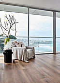 Throw on armchair next to glass wall with sea view