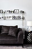 Pictures and plants on two picture ledges above dark grey sofa