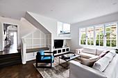 Offenes Wohnzimmer in gedeckten Farben, Sitzbank unter der Treppe