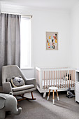 Rocking chair and cot in modern nursery decorated in grey