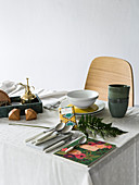 Gardening tools, crockery and cutlery on dining table with tablecloth