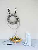 Garden hose coiled on antler-shaped, wall-mounted rack, basket and wellington boots