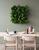 Devil's ivy in square green wall planter above dining table
