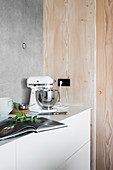 Mixer on kitchen counter against wood and concrete walls