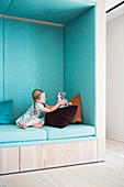 Girl playing in seating niche upholstered in pale blue