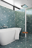 Free-standing bathtub in bathroom with patterned tiles on walls and floor