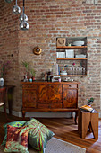 Antique sideboard against brick wall with shelves in niche